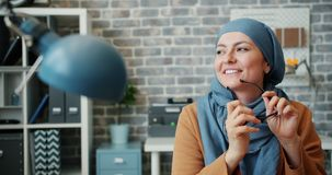 Happy mixed race girl in hijab smiling holding glasses in modern office. Sitting at desk alone enjoying work break. People, lifestyle and workplace concept stock footage