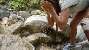 Happy mixed race hiker girl washes her face in clean cold mountain stream in the forest. Hd slowmotion. stock footage
