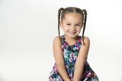 Smiling, biracial little girl in flowered sundress stock photo