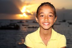 Happy mixed race school girl by seaside at sunset Stock Photos