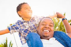 Happy Mixed Race Son and African American Father Playing Piggyback Out. Mixed Race Son and African American Father Playing Piggyback Outdoors Together Royalty Free Stock Photos