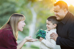 Happy Mixed Race Son Handing Gift to His Mom. Happy Young Mixed Race Son Handing Gift to His Mom As Father Stands Behind stock images