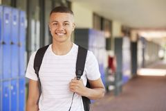 Happy mixed race teenage boy smiling in high school corridor stock photo
