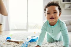 Happy mixed race toddler boy crawling in sitting room stock photo