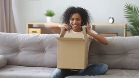 Happy mixed race woman sitting on couch opens received parcel