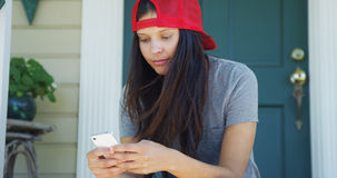 Happy mixed race woman texting on phone on porch Stock Photos