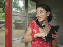 Happy Mixed Race Woman Using Public Phone Royalty Free Stock Photography