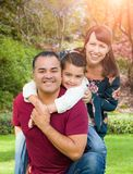 Happy Mixed Race Young Family Portrait At The Park. Happy Mixed Race Young Family Outdoor Portrait At The Park stock photo