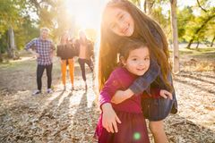 Happy Mixed Race Young Girl Sisters Outdoors with Family Behind. Mixed Race Young Girl Sisters Outdoors with Family Behind Them stock photo