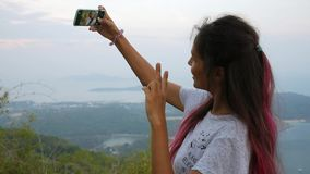 Happy Mixed Race Young Hipster Girl Taking Selfie on her Mobile Phone at Viewpoint. Phuket, Thailand. HD Slowmotion. stock video
