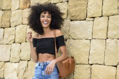 Happy mixed woman with afro hair laughing outdoors royalty free stock photo