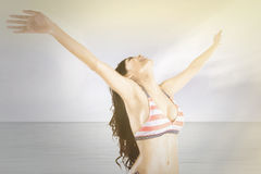 Happy model breathe fresh air at coast. Portrait of attractive woman breathe fresh air on the shore while wearing bikini and stretch her hands Stock Photo
