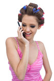 Happy model wearing hair rollers having a call. Happy young model wearing hair rollers having a phone call Royalty Free Stock Image