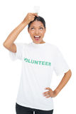 Happy model wearing volunteer tshirt holding light bulb above her head Stock Photos
