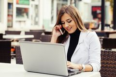 Woman working with a phone and laptop Stock Photography