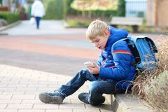 Happy modern boy with mobile phone. Teenager boy calling on mobile phone sitting outside of the school Royalty Free Stock Images
