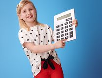 Happy modern child сlicking on button on calculator on blue stock images