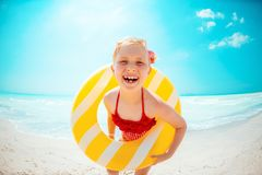 Happy modern child with yellow inflatable lifebuoy on beach stock photo