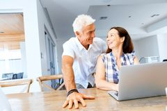 Happy modern mature couple working on laptop at home. Happy modern couple surfing the net and working on laptop at home royalty free stock image