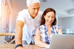 Happy modern mature couple working on laptop at home. Happy modern couple surfing the net and working on laptop at home stock photography