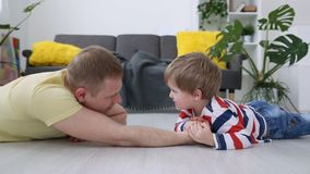 Happy modern family. Dad and his little son are measured by force on the floor in the living room. Happy modern family. Dad and his little son are measured by stock video footage