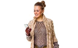 Happy modern fashion-monger in winter coat on white writing sms Stock Image
