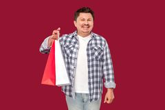Happy modern funny middle aged man in white t-shirt and checkered shirt standing and holding shopping packages with toothy smile. And looking at camera. indoor royalty free stock images