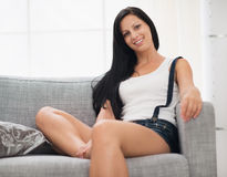 Happy girl sitting on couch in living room Stock Photos