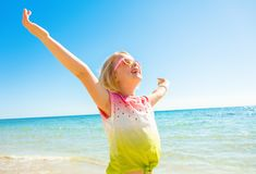 Happy modern girl in colorful shirt on seashore rejoicing Royalty Free Stock Images