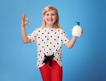 Happy modern girl showing liquid soap and ok gesture on blue. Happy modern girl in red pants showing liquid soap and ok gesture isolated on blue background stock images