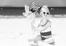 Happy modern girl on seacoast with windmill toy Royalty Free Stock Photography