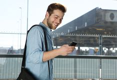 Happy modern man sending text message at airport Royalty Free Stock Photos