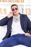 Happy modern man wearing sunglasses talking on the phone stock photography