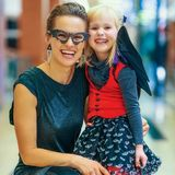 Happy modern mother and child on Halloween at mall. Trick or Treat. happy modern mother and child in bat costumes on Halloween at the mall stock photography