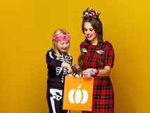 Happy modern mother and child looking at Halloween shopping bag Royalty Free Stock Photos