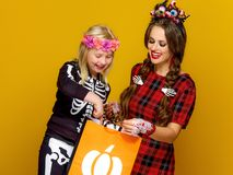 Happy modern mother and child looking at Halloween shopping bag Stock Photo