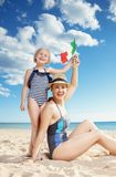 Happy modern mother and child on seashore showing Italian flag. Happy modern mother and child in beachwear on the seashore showing Italian flag stock photo