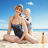 Happy mother and daughter on seacoast applying suntan lotion. Happy modern mother and daughter in swimwear on the seacoast applying suntan lotion royalty free stock image