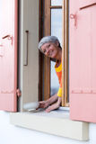 Happy modern senior woman. With white hairs looking from the window Royalty Free Stock Photo