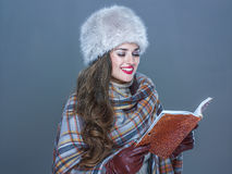 Happy modern woman in fur hat  on cold blue reading book Royalty Free Stock Photography