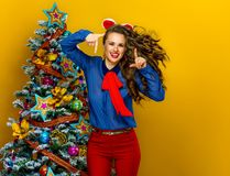 Happy modern woman near Christmas tree framing with hands Royalty Free Stock Image