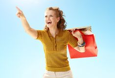 Woman with shopping bags pointing at something against blue sky. Happy modern woman with shopping bags pointing at something against blue sky royalty free stock image