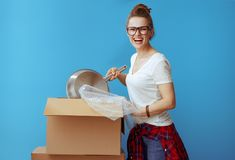 Happy modern woman in white t-shirt on blue packing stuff stock photography