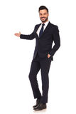 Happy modern young business man presenting and smiling stock photo