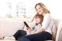 Happy mom and adorable daughter watching tv Royalty Free Stock Photo