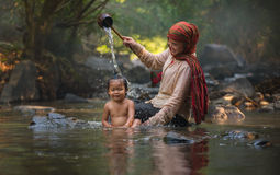 Happy mom and baby child (Mother's Day). Happy Asia mom and child Play water shower at stream nature Stock Image