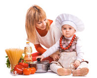 Happy mom and baby are cooking on the kitchen. Stock Photo