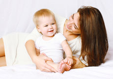 Happy mom and baby having fun in bed at home Stock Images