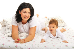 Happy mom and baby laying in bed Stock Photography