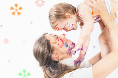 Happy mom and baby playing with painted face by paint Royalty Free Stock Images
